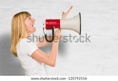 Woman Holding Megaphone against a concrete background - stock photo