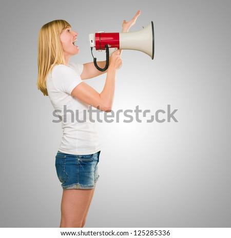 Woman Holding Megaphone against a grey background - stock photo