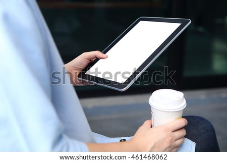 Woman holding mockup tablet and holding coffee cup with office background
