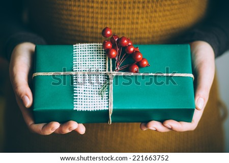 Woman holding modern Christmas present gift - stock photo
