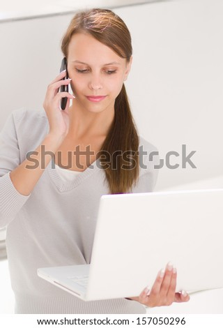 woman holding on laptop and talking on the phone