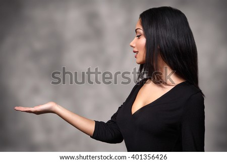Woman holding or presenting something - stock photo