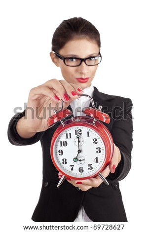 Woman holding out a clock showing 7 o'clock isolated on white. Focus is on alarm. - stock photo