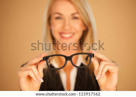 Woman holding out her spectacles or glasses with dark frames at arms length with selective focus to the glasses