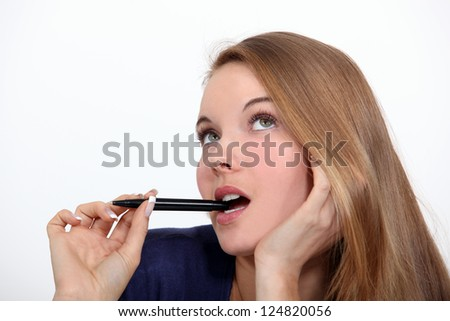Woman holding pen to mouth - stock photo