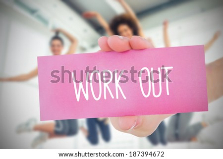 Woman holding pink card saying work out against dance class in gym - stock photo