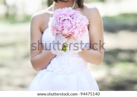 Woman holding pink wedding flowers bouquet - stock photo