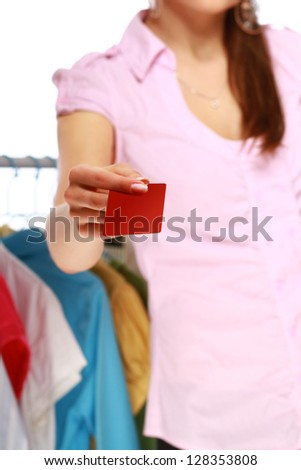 Woman holding plastic card while going shopping