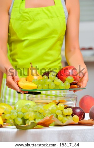 woman holding plate with fruits