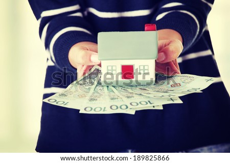 Woman holding PLN ( polish zloty ) bills and house model  - real estate loan concept - stock photo