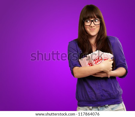 Woman Holding Popcorn Empty Packet Isolated On Purple Background - stock photo