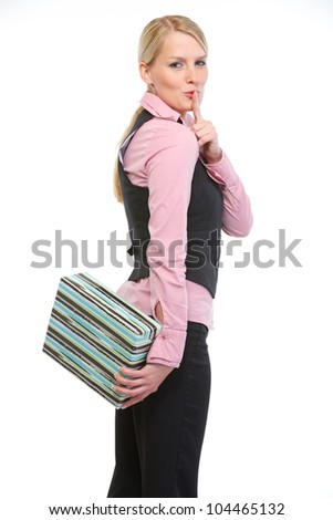 Woman holding present box behind back and showing shh gesture - stock photo