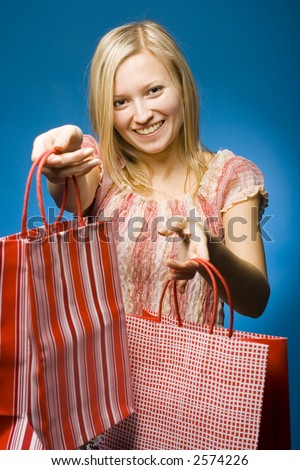 Woman holding red carrier bags. Smile on her face. - stock photo