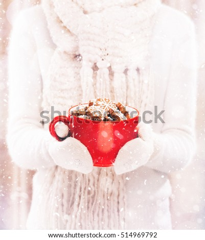 Woman holding red cup with nice Christmas cookies close up on light background with snowfall. Hands in woolen gloves holding a cozy mug with sweet holiday food. Winter and Christmas time concept.