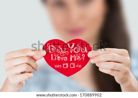 Woman holding red heart with question: Do you love Me? - stock photo