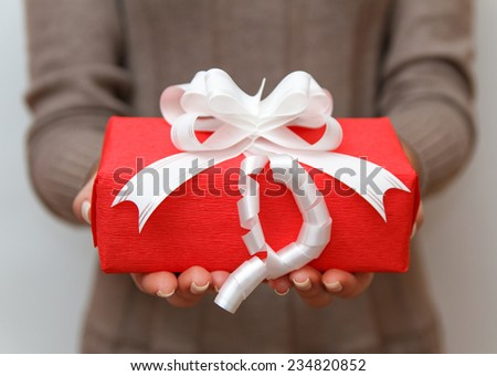 Woman holding red present box with white ribbon - stock photo