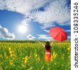 Woman holding red umbrella in Yellow flower field and cloud sky - stock photo