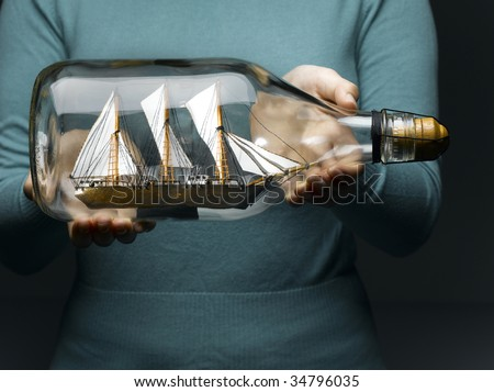 Woman holding sailing ship in bottle, mid section