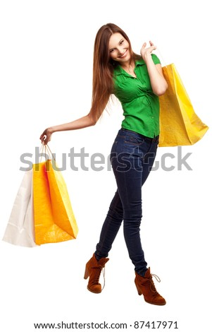 Woman holding shopping bags against a white background - stock photo