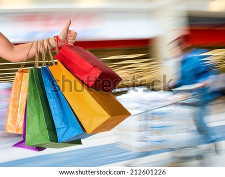 Woman holding shopping bags and gesturing thumb up at shopping mall