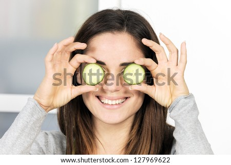 Woman holding slice of cucumber over eye - stock photo