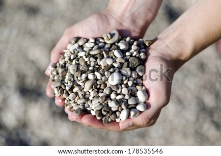 Woman holding small pebbles in her hands.
