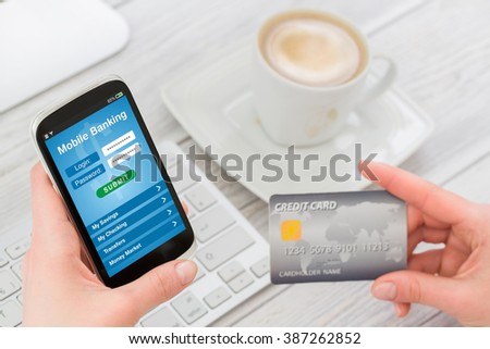 Woman holding smart phone with mobile banking application on a screen. All visible graphics and illustrations are our own design, and were produced for this particular shoot. - stock photo