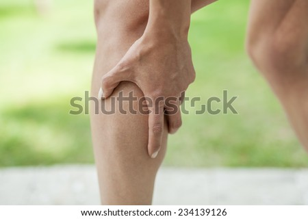 Woman holding sore leg muscle while jogging. Cramp in leg calves. Sports injury concept. - stock photo
