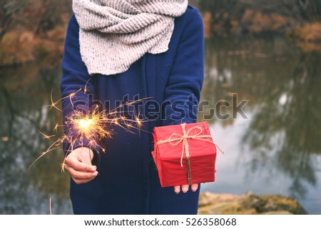 Woman holding sparkler and box gift in forest, winter day