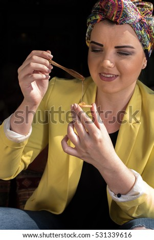 woman holding spoon full of honey