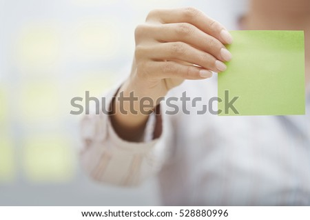 Woman holding sticky note with empty space