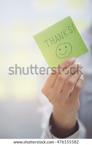 Woman holding sticky note with Thanks text