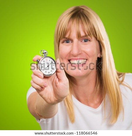 Woman Holding Stopwatch against a green background - stock photo