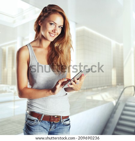 Woman holding tablet computer in hall shoping center. Working on touching screen - stock photo