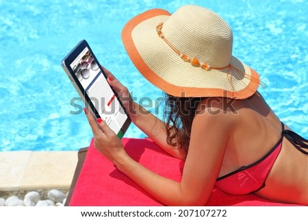 Woman holding tablet computer in the pool - stock photo