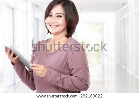 Woman holding tablet computer isolated on white background - stock photo