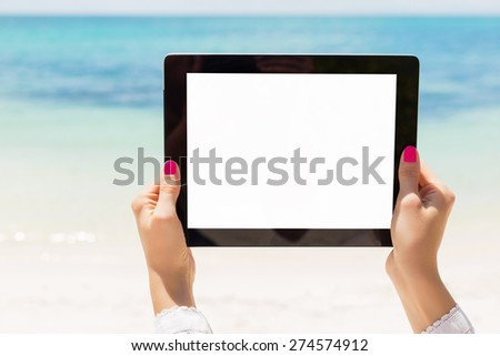 Woman holding tablet computer with empty screen on the beach - stock photo