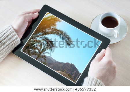 Woman holding tablet pc with beautiful mountain view, planning vacations, booking trip  - stock photo