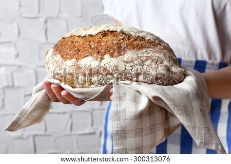Woman holding tasty fresh bread, close up - stock photo
