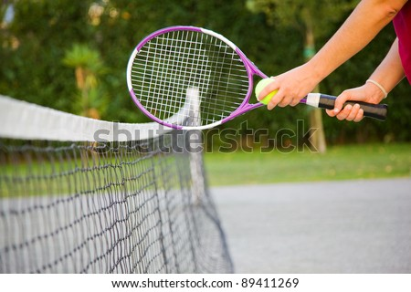 Woman holding tennis racket and ball close to the net - stock photo