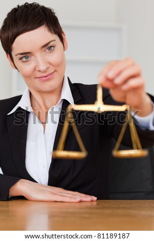 Woman holding the justice scale in her office - stock photo