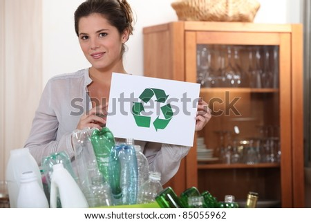Woman holding the universal recycling sign - stock photo