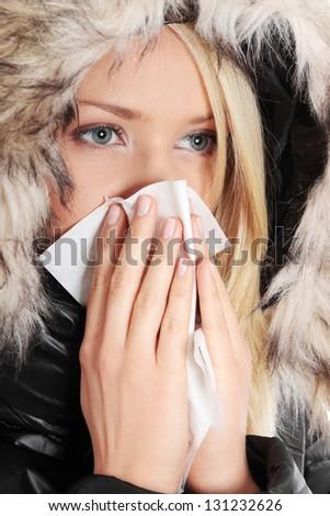 Woman holding tissue and sneezing isolated on white background - stock photo