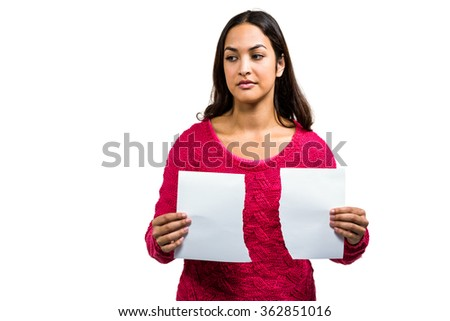 Woman holding torn documents while standing on white background