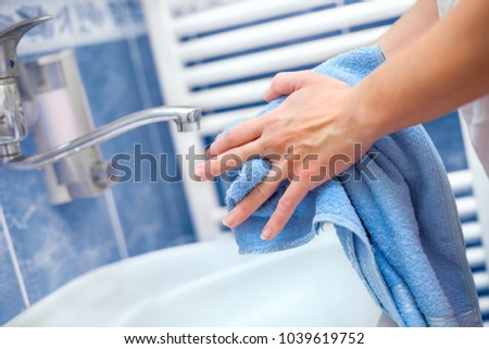 Woman holding towel and drying hands in bathrrom