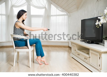 Woman holding tv remote and pointing on the tv in the room - stock photo