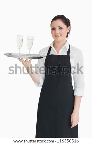 Woman holding two glasses on a silver tray - stock photo