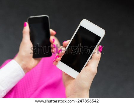 Woman holding two mobile phones - stock photo