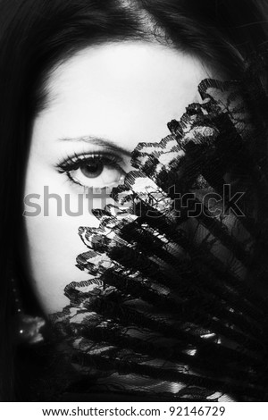 woman holding up a fan to her face - stock photo