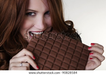 woman holding up a large bar of chocolate - stock photo